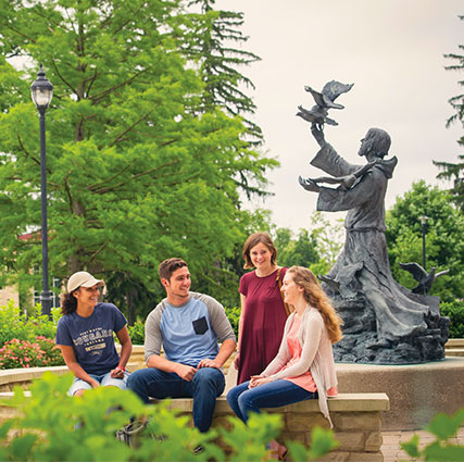 A group of 4 students are sitting on a bench outside of Brookside in front of the St. Francis statue